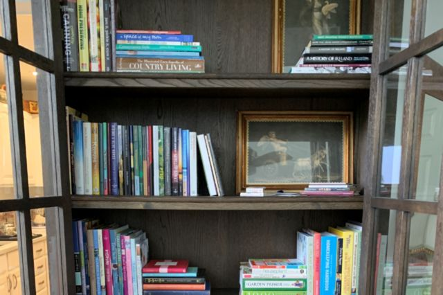 books and framed pictures on a bookcase