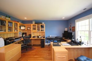 office with wooden desk, shelves, and floor